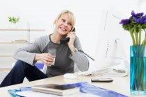 Businesswoman talking on phone at work — Stock Photo