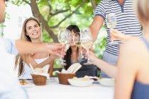 Amigos brindando entre sí al aire libre, enfoque selectivo - foto de stock