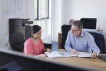 Donna d'affari e uomo d'affari seduti a tavola in ufficio e ad analizzare i documenti cartacei — Foto stock