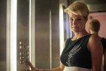 Бизнесвумен нажимает кнопку лифта — стоковое фото