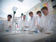 Profesor de ciencias y estudiantes realizando experimentos en laboratorio escolar - foto de stock
