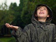 Girl holding hand out to catch rain — Stock Photo