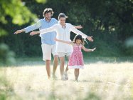 Семья весело гуляет по загородному полю — стоковое фото