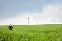 Donna incinta che cammina attraverso il parco eolico — Foto stock