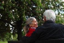 Vieux couple assis sur un banc de parc — Photo de stock