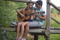 Coppia adolescente che suona la chitarra e canta — Foto stock