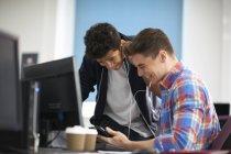 Junge männliche College-Studenten am Computerpult lachen, während sie Kopfhörer hören — Stockfoto