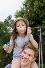 Ragazza con bolle sulle spalle dei padri — Foto stock