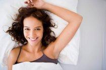 Giovane donna a letto sorridente alla macchina fotografica — Foto stock