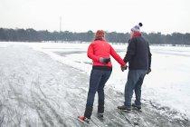 Пара лед коньки, взявшись за руки — стоковое фото
