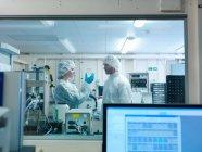 Os cientistas que desgastam a roupa protetora em um laboratório, olham um alvo da fusão junto — Fotografia de Stock