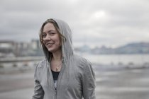 Portrait of young female runner wearing hoody on windy dockside — Stock Photo