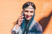 Jovem com mergulho tingido o cabelo azul falando no smartphone em frente a parede laranja — Fotografia de Stock