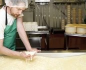 Cheesemaker with handful of curds at farm factory — Stock Photo