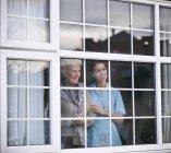 Enfermeira e mulher sênior que olham fora do indicador da casa — Fotografia de Stock