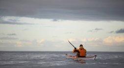 Вид сзади человека гребля на каноэ в стоячей воде — стоковое фото