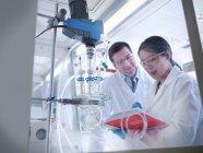 Scientifiques féminins et masculins avec ordinateur portable inspectant l'expérience en laboratoire — Photo de stock