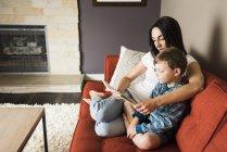 Мати для навчання сина, щоб читати книги на дивані будинку — стокове фото