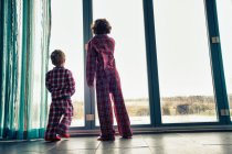 Rear view of boys in pajamas looking out window — Stock Photo