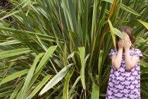 Молодая девушка прячет лицо травяными левами — стоковое фото