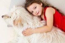 Menina relaxante na cama com o cão — Fotografia de Stock