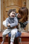 Mother and daughter on doorstep laughing — Stock Photo