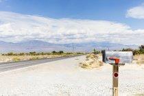 Briefkasten auf Landstraße unter blauem Himmel — Stockfoto