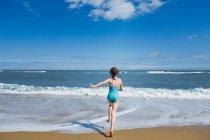 Заднього вигляду дівчинка нарватися на море — стокове фото