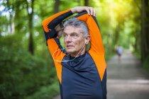 Corredor masculino sênior, aquecendo-se no parque da floresta — Fotografia de Stock