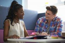 Молодые девушки и студенты колледжей обсуждают за столом — стоковое фото