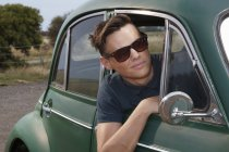 Young man leaning out of vintage morris minor — Stock Photo