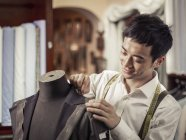 Trainee tailor pinning garment in traditional tailors shop — Stock Photo