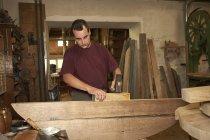 Arbeiter hämmert Holz in Geschäft — Stockfoto