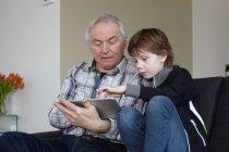 Старший мужчина с внуком, использующий цифровой планшет дома — стоковое фото