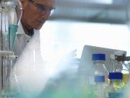 Scientifique examinant les données d'un ordinateur portable provenant d'une expérience en laboratoire — Photo de stock