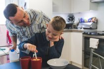 Father and son in kitchen, son stirring hot drink — Stock Photo