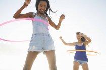 Dos mujeres jóvenes usando hula hoop en la playa - foto de stock