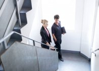 Man and woman walking up stairs — Stock Photo