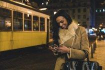 Junge Frau in der Stadt bei Nacht, mit Smartphone, Lissabon, Portugal — Stockfoto