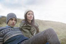 Young couple sitting on beach, Brean Sands, Somerset, England — Stock Photo