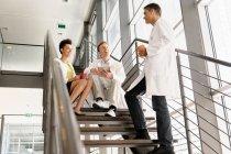 Doctors talking on steps in hospital — Stock Photo