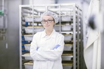 Factory worker wearing overall and hair net looking at camera — Stock Photo