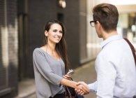 Молодой бизнесмен и деловая женщина пожимают руку за пределами офиса, Лондон, Великобритания — стоковое фото