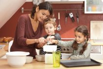 Mother and children cooking in kitchen — Stock Photo