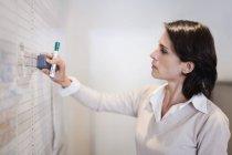 Portrait of Businesswoman erasing whiteboard — Stock Photo