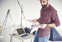Мужчина-фотограф смотрит на фотографии с фотосессии в студии — стоковое фото