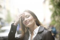 Porträt einer schönen Frau mit langen braunen Haaren auf der Straße der Stadt — Stockfoto