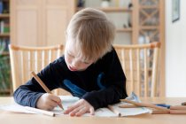 Boy drawing with colored pencils, focus on foreground — Stock Photo