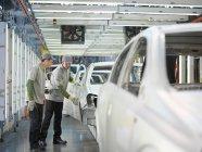 Lavoratori dello stabilimento auto discutendo automobili — Foto stock