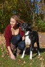 Женщина выгуливает собаку в осенних листьях — стоковое фото